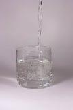 A água é derramada em um vidro Fotografia de Stock