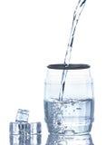 A água é derramada em um vidro Fotografia de Stock Royalty Free