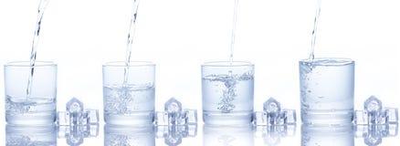 A água é derramada em um vidro com cubos de gelo Fotos de Stock