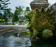 A água é liberada da boca das estátuas no palácio da água de Taman Ujung Imagem de Stock