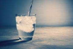 água abstrata que derrama no vidro da água com gelo no vintage c Imagens de Stock Royalty Free