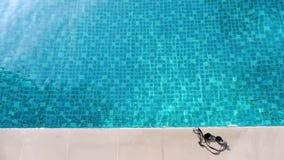 A água azul da piscina e os óculos de proteção dos olhos no verão e as telhas de assoalho brancas da barra lateral no hotel para  vídeos de arquivo
