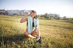 Água bebendo da menina do esporte após o esporte Menina que senta-se na grama Construção no fundo Foto de Stock Royalty Free