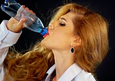Água bebendo da mulher do frasco Bebida sedento do terno de negócio da menina imagem de stock