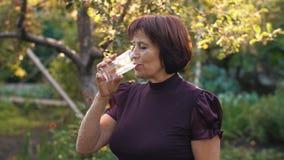 Água bebendo da mulher idosa video estoque