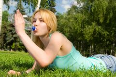 Água bebendo da mulher no glade do verão imagem de stock