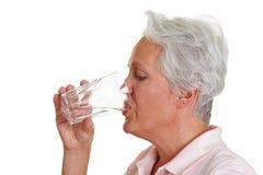 Água bebendo da mulher sênior fotografia de stock