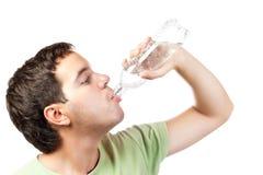 Água bebendo de homem novo do frasco isolado Imagem de Stock Royalty Free