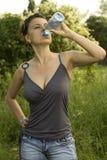 Água bebendo de mulher nova de um frasco Fotografia de Stock