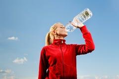 Água bebendo de mulher nova do frasco plástico Fotografia de Stock Royalty Free