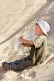 Água bebendo do menino novo na areia Fotos de Stock