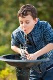 Água bebendo do miúdo bonito em um parque fotografia de stock