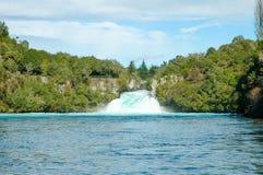 A água cai contra uma floresta verde e uns céus azuis Fotografia de Stock