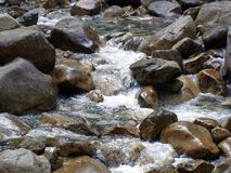 A água cai espirrando abaixo das rochas com sua opinião natural fotos de stock