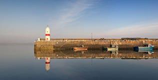 A água calma do porto, do farol e dos barcos reflete Imagens de Stock
