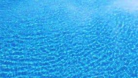 Água clara de ondulação na piscina com parte inferior azul, vista superior filme