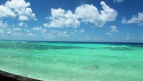 Água clara do oceano dos azuis celestes no fundo do céu azul e das nuvens brancas filme