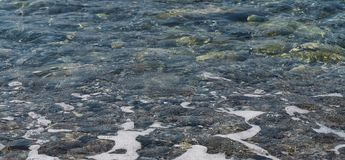 Água clara e seixos coloridos no mar fotografia de stock