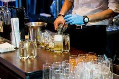 Água com gás de derramamento da mão do barman no gelo e no uísque Fotos de Stock
