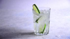 A água com gelo e cal das fatias derrama no vidro Movimento lento Refrescar a bebida do verão video estoque