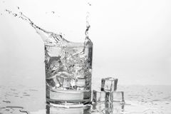 A água com gelo em um vidro com espirra imagem de stock royalty free