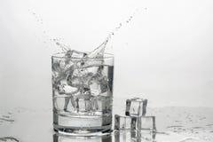 A água com gelo em um vidro com espirra foto de stock