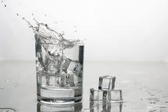 A água com gelo em um vidro com espirra fotografia de stock