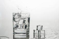 A água com gelo em um vidro com espirra foto de stock royalty free