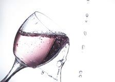 Água cor-de-rosa que está sendo derramada em um vidro de vinho Foto de Stock Royalty Free