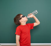 Água da bebida da estudante da garrafa perto de um quadro-negro, espaço vazio, conceito da educação Fotos de Stock