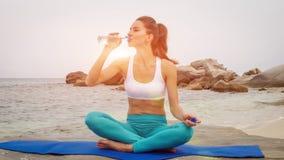 A água da bebida da mulher da aptidão após ter feito o esporte exercita na praia no por do sol imagem de stock