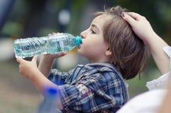 Água da bebida do rapaz pequeno imagem de stock