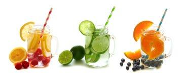 Água da desintoxicação com fruto em uns frascos de pedreiro isolados no branco Imagens de Stock Royalty Free