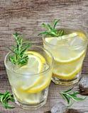 Água da desintoxicação com limão e alecrins cortados em uns vidros na tabela Imagens de Stock Royalty Free