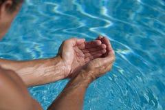 Água da terra arrendada do homem em sua mão Imagens de Stock Royalty Free