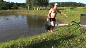 A água da tração do homem do jardineiro da lagoa com cubeta e derrama dentro o tanque vídeos de arquivo