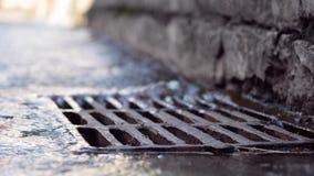 Água de chuva que cai no sistema de drenagem do esgoto fotografia de stock