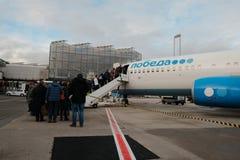 Água de Colônia, Alemanha, 16 de dezembro de 2017: Passageiros que obtêm a bordo de uma empresa do coster das Pobeda-linhas aérea Foto de Stock Royalty Free