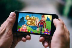 ÁGUA DE COLÔNIA, ALEMANHA - 27 DE FEVEREIRO DE 2018: O jogo do App da saga do esmagamento dos doces jogou no iPhone de Apple foto de stock