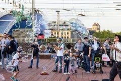 ÁGUA DE COLÔNIA, ALEMANHA 6 DE OUTUBRO DE 2018: Turistas de passeio que olham bolhas de sopro de um indivíduo fotografia de stock