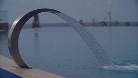 Água de derramamento da cachoeira da piscina na área de recurso no dia de verão ensolarado filme