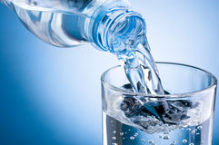 Água de derramamento da garrafa no vidro no fundo azul