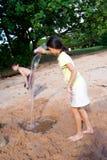 A água de derramamento da menina no escavado para fora fura na areia Fotos de Stock Royalty Free