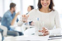 Água de derramamento da mulher agradável no vidro Fotografia de Stock