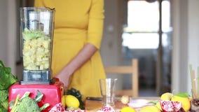Água de derramamento da mulher no misturador com abacaxi e abacate vídeos de arquivo