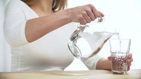 Água de derramamento da mulher no vidro do close up do jarro video estoque