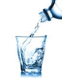 Água de derramamento do frasco no vidro Imagem de Stock