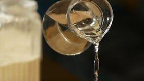 Água de derramamento do jarro de vidro na farinha para a massa que prepara-se na cozinha vídeos de arquivo