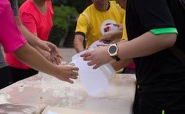 Água de derramamento dos povos voluntários para o corredor de maratona dos atletas Fotografia de Stock