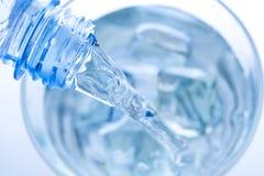 Água de derramamento em um vidro elegante com gotas do gelo e da água Fotografia de Stock